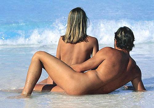 Couple naked sitting on beach